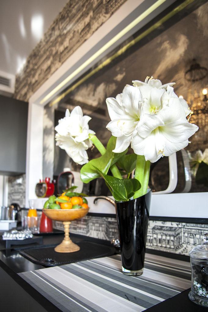 tavolo con fiori, cesto di frutta, specchio a muro